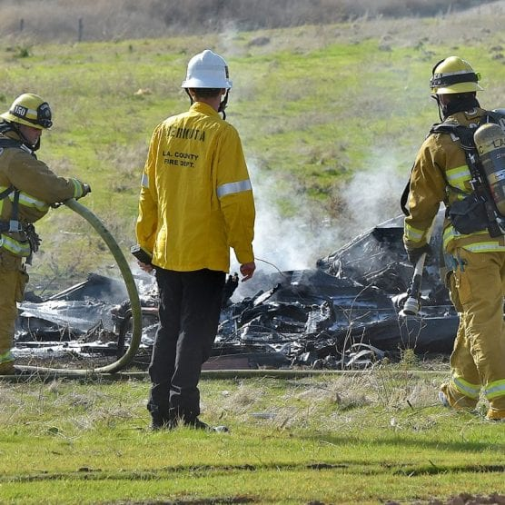 Firefighters work around the smoldering wreckage of a small airplane that crashed near the 14 Freeway and Newhall Avenue in Newhall on Saturday, January 4, 2020.   Photo: Dan Watson / The Signal.