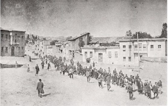 Armenian people are marched to a nearby prison in Mezireh by armed Ottoman soldiers. Kharpert, Ottoman Empire, April 1915.   Photo: Public Domain.