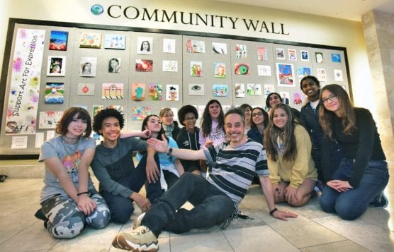 "Rio Norte Junior High School art teacher Daryl Bibicoff, center, and his seventh- and eighth-grade students pose in front of their SAFE ""Support Art For Expression"" exhibit on the Community Wall in the Westfield Valencia Town Center on Friday, February 7, 2020. 